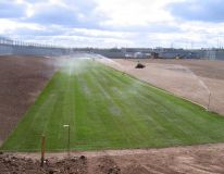 Watering-in Big Roll turf at HMP Featherstone, Wolverhampton. Construction and a new rugby pitch.A total of 10,000 sq metres of turf laid.
