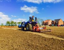 Spring 2015, Healing near Grimsby. Compact tractor and 1.5 metre RotaDairon preparing the public open space for grass seeding on a new housing development site.